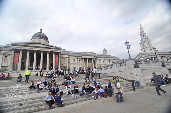 National Gallery, Trafalgar Square, London, showing crowd of people sitting at steps