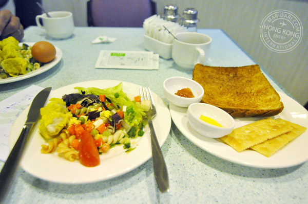 Evergreen Hotel Hong Kong buffet breakfast spread - spiral pasta with sweet tomato sauce, wonton, hard-boiled eggs, fresh salad with dressing, bread, crackers, jam and butter, coffee