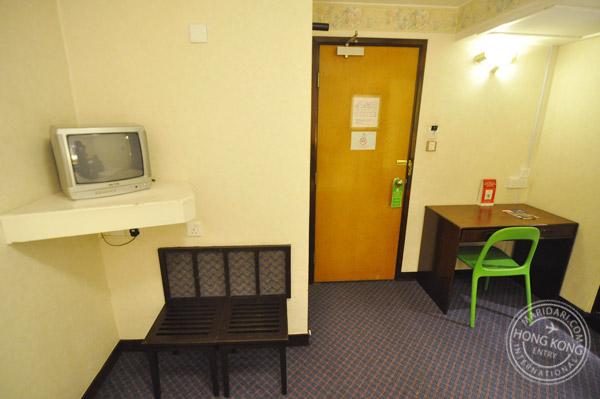 Evergreen Hotel Hong Kong no-window twin bedroom - TV, writing desk, chair, bench, carpet